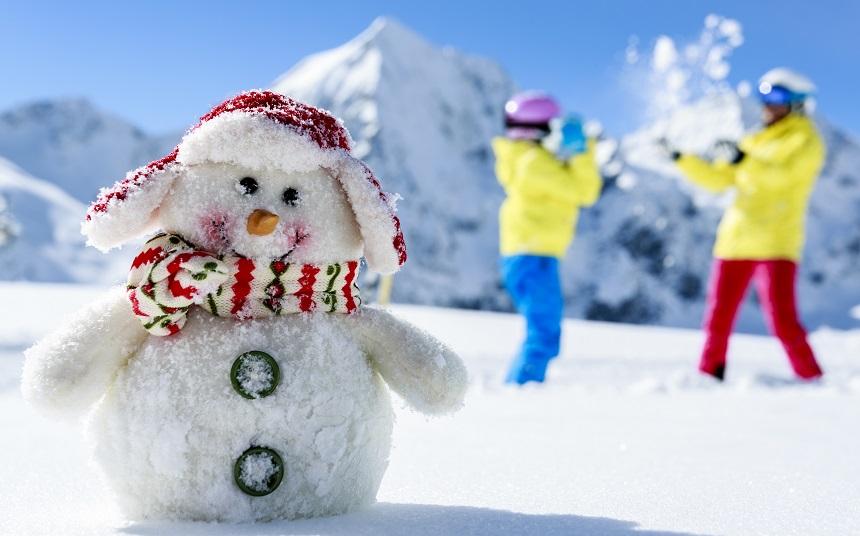 Ski, skiers with snowman enjoying winter